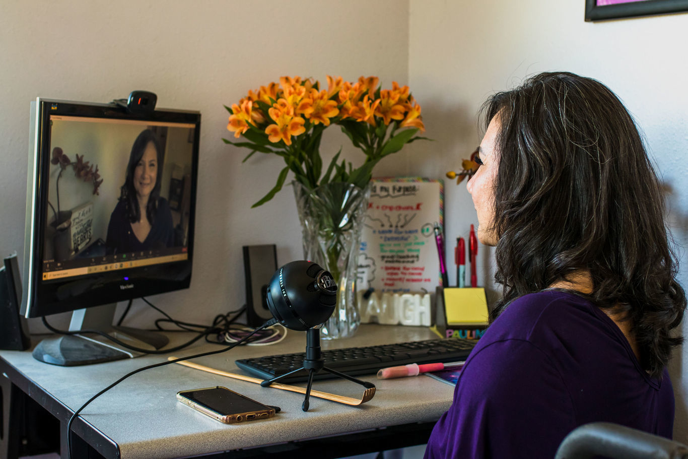 Woman with tan skin and dark hair taking a video on the computer.