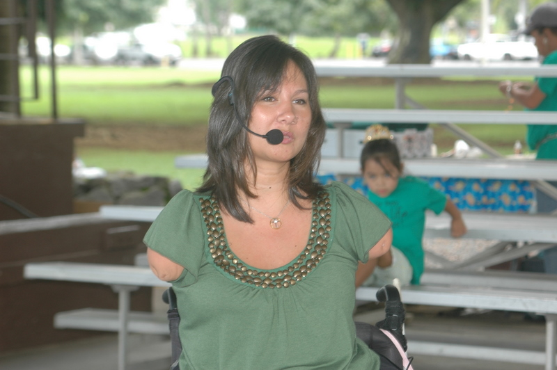 Woman with tan skin and dark hair and green shirt speaking into a headset microphone.